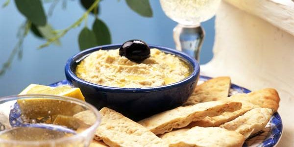 Hoummous hummus with pitta bread olives & retsina wine glass bottle lemon bay leaves blue dish in b/; keywords greek healthy snack